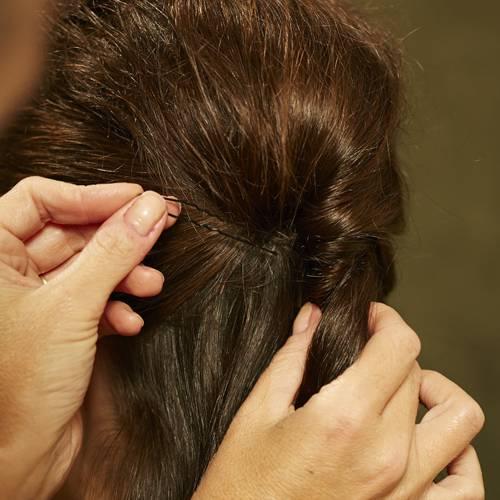 Frisuren: Stück für Stück weiter nach unten einschlagen. Am Ende die Haare zu einem Zopf zusammenbinden und mit einer Strähne das Haargummi umwickeln. Gut mit Haarspray benebeln.