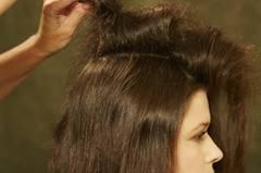 Einen Mittelscheitel ziehen und die Haare auf einer Seite mit Haarspray und Kamm antoupieren.