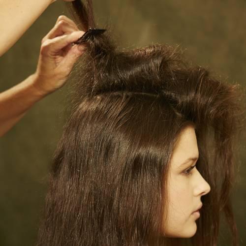 Frisuren: Einen Mittelscheitel ziehen und die Haare auf einer Seite mit Haarspray und Kamm antoupieren.