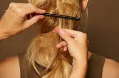 Einzelne Partien des Zopfes vorsichtig mit einem Kamm antoupieren und mit Haarspray besprühen.
