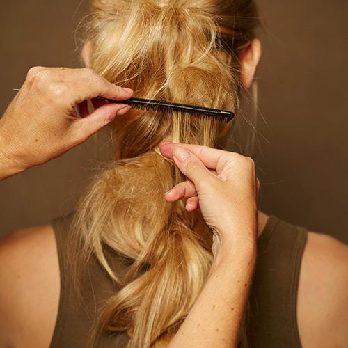 Frisuren: Einzelne Partien des Zopfes vorsichtig mit einem Kamm antoupieren und mit Haarspray besprühen.