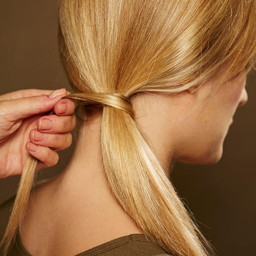 Frisuren: Besonders hübsch wird das Ergebnis, wenn die Strähne möglichst gleichmäßig um den Zopf gelegt wird.