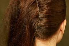Die Haare von der anderen Seite glatt nach hinten kämmen und entlang des Mittelscheitels am Hinterkopf mit Klammern feststecken.