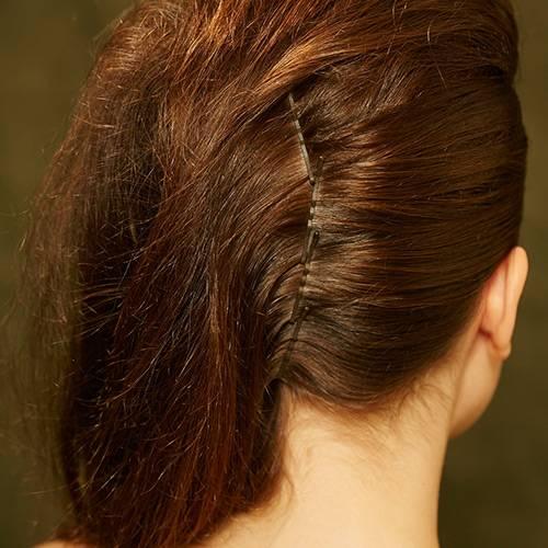 Frisuren: Die Haare von der anderen Seite glatt nach hinten kämmen und entlang des Mittelscheitels am Hinterkopf mit Klammern feststecken.