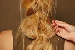 Anschließend ein dünnes Leder- oder Baumwollband anstelle des Haargummis um das Zopfende wickeln und vorsichtig in das Flechtwerk einfädeln.