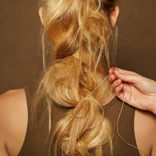 Frisuren: Anschließend ein dünnes Leder- oder Baumwollband anstelle des Haargummis um das Zopfende wickeln und vorsichtig in das Flechtwerk einfädeln.