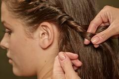 Zunächst werden alle Haare nach hinten gebürstet. Dann an einer Seite - vom Pony aus beginnend - die Haare am Ansatz nach innen eindrehen.
