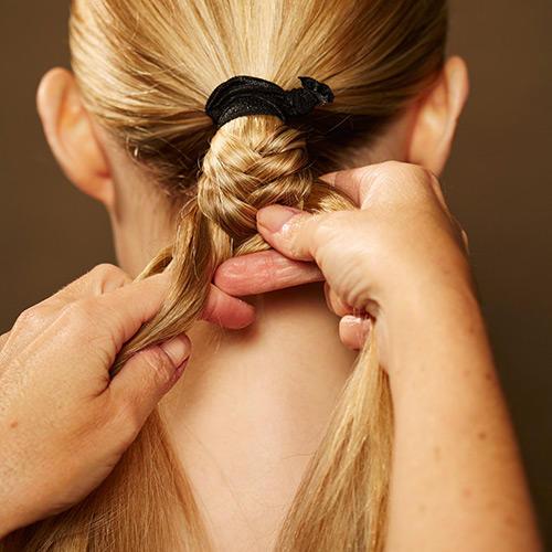 Frisuren: Den Zopf in zwei gleich große Stränge eingeteilen. Dann abwechselnd eine feine Strähne von einem der Stränge abteilen und zum anderen Strang dazunehmen.