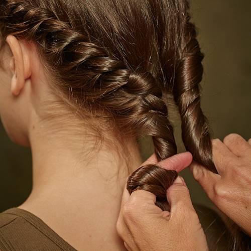 Frisuren: Das Ganze auf der anderen Seite wiederholen. Beide Kordeln im Nacken ineinander wickeln und mit einem Haargummi fixieren. Eine kleine Strähne von der Zopfunterseite abteilen, um das Haarband wickeln und mit einer Klammer möglichst unsichtbar wegstecken.