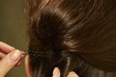 Die toupierte Partie gemeinsam mit den restlichen Haaren zu einem Strang fest eindrehen. Mit langen Klammern fixieren.