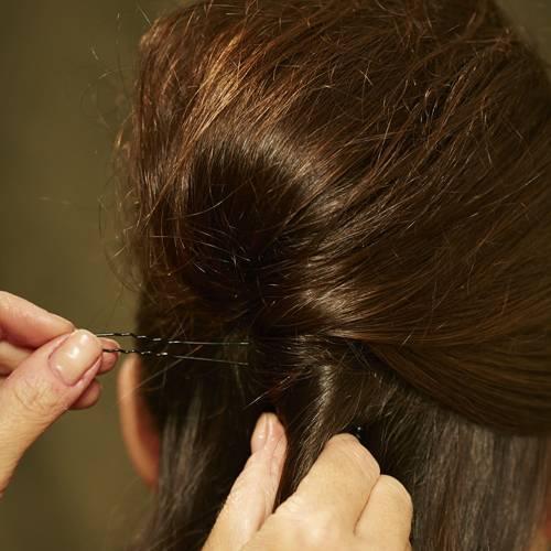 Frisuren: Die toupierte Partie gemeinsam mit den restlichen Haaren zu einem Strang fest eindrehen. Mit langen Klammern fixieren.