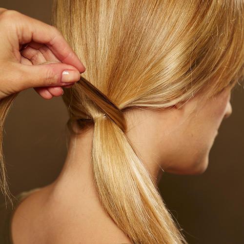 Frisuren: Von der Unterseite des Zopfes eine schmale Strähne abtrennen und um den Zopf wickeln.