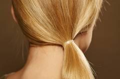 Haare erst gut durchbürsten, dann mit einem transparenten Haargummi einen seitlichen, tief im Nacken sitzenden Zopf binden.