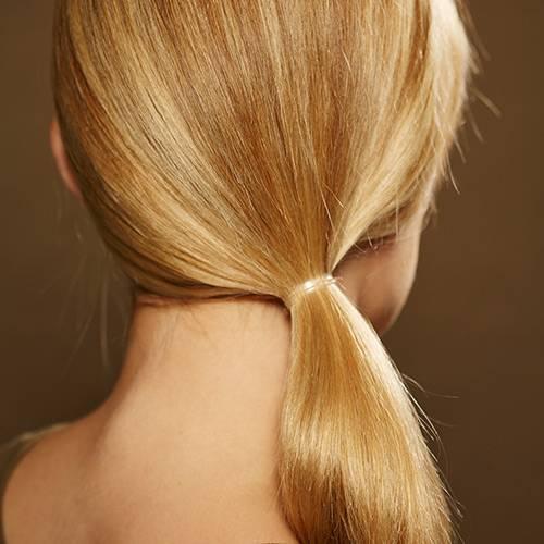Frisuren: Haare erst gut durchbürsten, dann mit einem transparenten Haargummi einen seitlichen, tief im Nacken sitzenden Zopf binden.