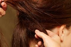 Mit Klammern unter dem Zopf feststecken. Darauf achten, dass die Haare nicht zu streng anliegen. Anschließend vorsichtig ein paar Strähnen am Oberkopf rauszupfen, mit Haarspray fixieren. Dadurch bekommt diese Frisur ihren leicht zersausten Look.