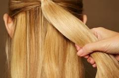 Die Haare nach hinten kämmen. Die obere Partie am Oberkopf abteilen und mit einem unsichtbaren Haargummi zusammenbinden.