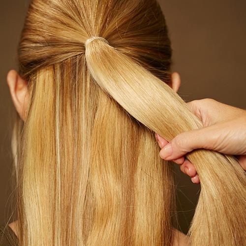 Frisuren: Die Haare nach hinten kämmen. Die obere Partie am Oberkopf abteilen und mit einem unsichtbaren Haargummi zusammenbinden.