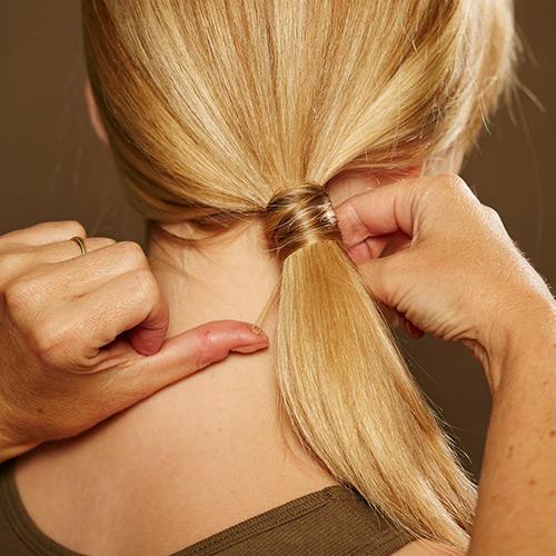 Frisuren: Das Ende der Strähne mit einer Klammer möglichst unsichtbar feststecken. Am wenigsten fallen Spangen auf, wenn sie den gleichen Ton der Haarfarbe haben.