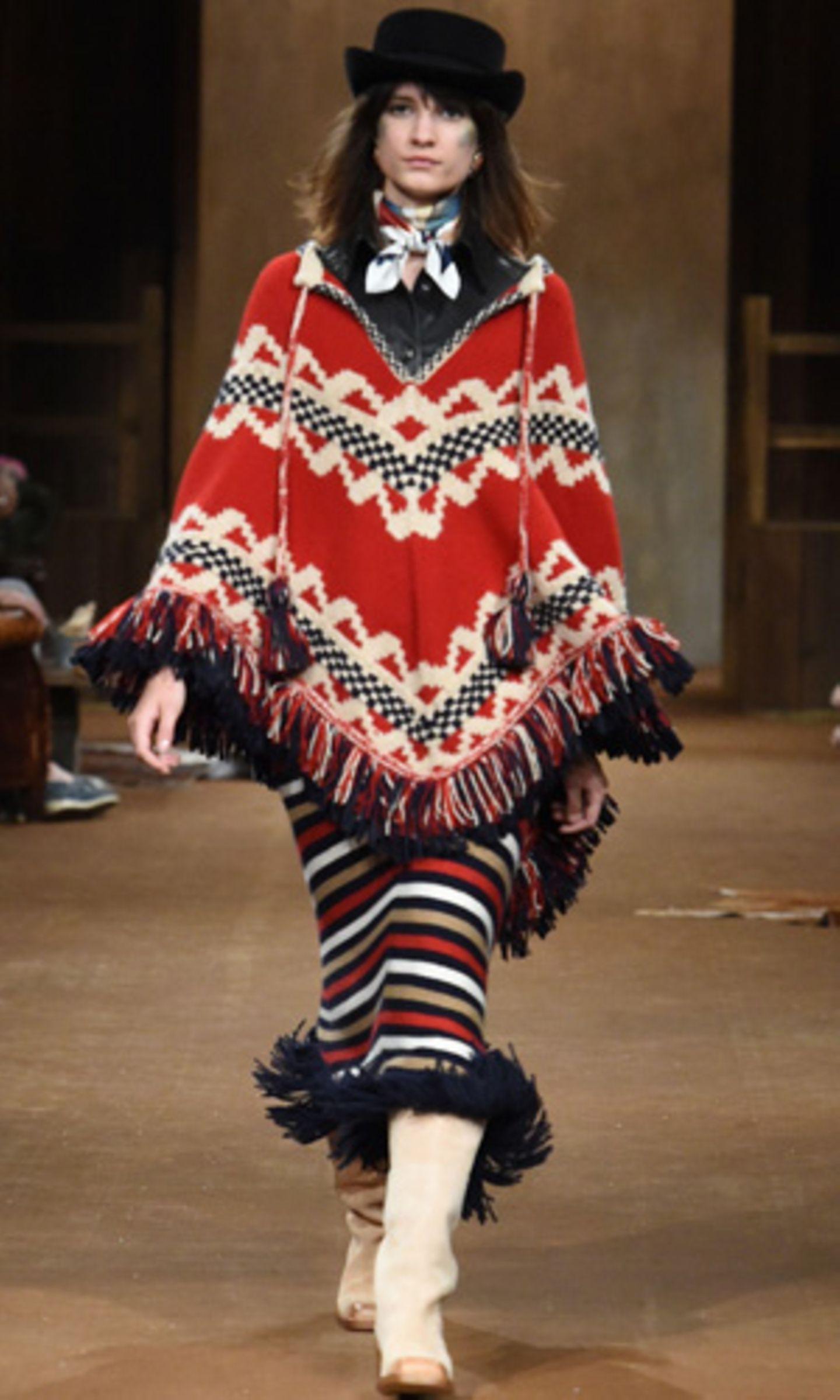 """Angefangen hat es mit der """"Paris-Dallas""""-Kollektion von Chanel: Als Karl Lagerfeld die Gäste seiner Modenschau in einer überdimensionalen Scheune empfing und Models in neu interpretierten Western-Looks über den staubigen Laufsteg schickte, war (wie so oft bei Chanel) ein neuer Trend geboren. Oder besser gesagt: Ein Trend-Revival, denn Western-Elemente waren in der Mode schließlich schon häufiger zu sehen. Das Neue: Diesen Herbst wird Indio-Mode bunt mit Western-Klassikern gemischt. Die Rede ist von Wollponchos, Fransen, Lederboots, Karohemden und handgemachten Details."""