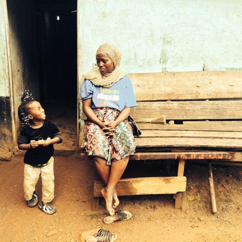 """Esther und ihre Tochter Katie sind gesund, aber Esther weiß, dass viele ihrer Nachbarn krank sind. Die Weltgesundheitsorganisation warnt, dass die Zahl der Ebola-Fälle auf mindestens 20.000 steigen könne, sollte die Seuche nicht entschlossener bekämpft werden. In Guinea, Liberia und Sierra Leone wurden bisher mehr als 5800 Infizierte registriert, von denen mindestens 2800 starben. Die Gespräche über Ebola konzentrieren sich oft auf diese Zahlen. Doch dahinter stecken Tausende von Schicksalen echter Menschen. Die Organisation """"More Than Me"""" gibt der Krankheit ein Gesicht - mit Bildern von Frauen und Mädchen, die ihren Schmerz, ihren Verlust und ihre Hoffnung widerspiegeln. Die Nonprofit-Organisation macht sich für Mädchen stark, die im West Point Slum in Liberias Hauptstadt Monrovia leben. Ihre """"More Than Me Academy"""" ist die erste kostenlose, reine Mädchenschule des Landes. Zusätzlich zum Unterricht bekommen die Mädchen dort zwei Mahlzeiten am Tag und werden ärztlich versorgt. Es gibt Computer, eine Bücherei und ein umfassendes Nachmittagsprogramm. Wenn Sie die Arbeit von """"More Than Me"""" unterstützen wollen, können Sie hier spenden."""