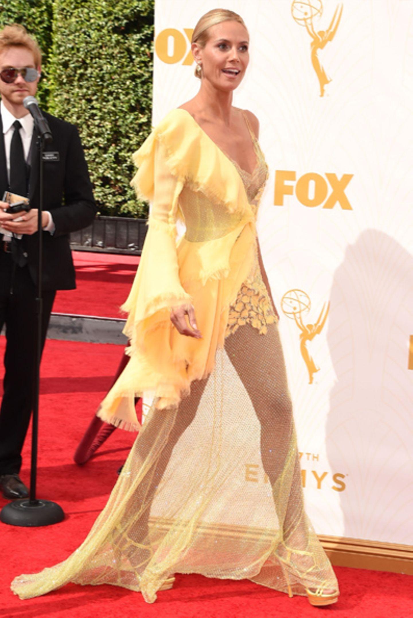 """Nachdem der """"Naughty Spoon"""" auf ihrem entblößten Hinterteil für jede Menge Aufgregung gesorgt hat, kündigt sich in dem Bibo-gelben Chiffon-Fetzen nun der nächste Shitstorm an. Unser Flop 1: Heidi Klum in einem gelben Alptraum-Kleid von Versace."""