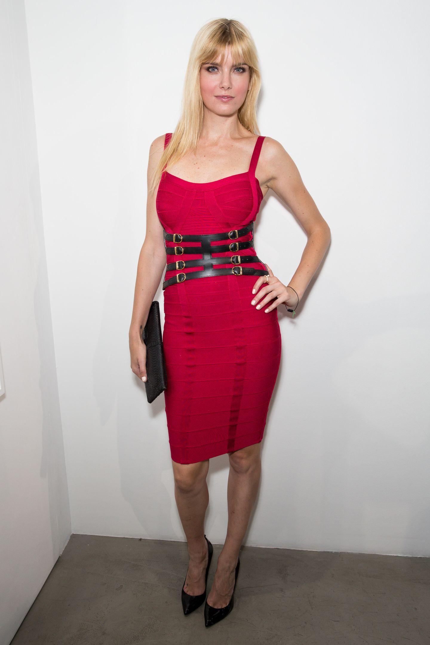 Hingucker in Knallrot: Model Eugenia Kuzmina trägt ein Bandage-Dress mit dünnen Trägern und dazu einen auffälligen schwarzen Taillengürtel.