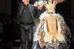 Hier ist Jean Paul Gaultier mit einem Model der Show und seiner Kreation zu sehen. Der lange, schmale Hut gehört zur bretonischen Tracht dazu und wird von dem Designer für seine Show modern interpretiert.