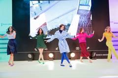 Nicht nur sportlich, sondern auch passend gekleidet für den Stadtbummel. Tänzerin Di in der Mitte trägt: Pullover und Mantel von Marc Cain, Leggins von Only und Schuhe von Ilse Wahl über gymhall.de.