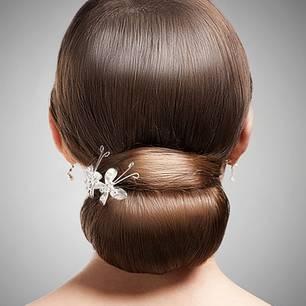 Ballerina-Dutt für Langhaarige: Einen Seitenscheitel ziehen, Haare streng zurück kämmen und mit einer breiten Spange zum Pferdeschwanz stecken. Eine Strähne an der Unterseite des Schwanzes herauslösen, sie wird später über die Spange gelegt. Je nach Haarlänge den Schwanz entweder über ein Haarkissen zum Dutt stecken oder, bei überschulterlangem Haar, es mehrmals über die Hand zum Dutt legen und mit einer zweiten Spange tief im Nacken befestigen. Zuletzt die Extrasträhne glatt über die Spange legen, feststecken.