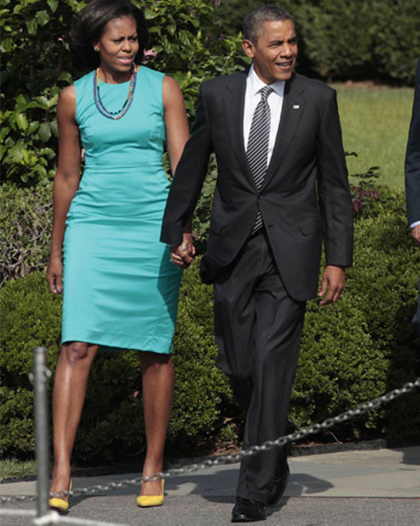 Im September vorm Weißen Haus: Michelle Obama Hand in Hand mit ihrem Präsidenten. Zum türkisen Etuikleid kombiniert sie sonnengelbe Pumps.