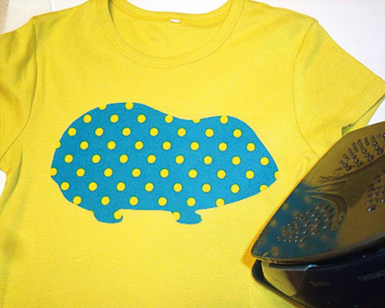 Tierkörper auf dem T-Shirt platzieren und aufbügeln (Stufe 3 bzw. so heiß, wie es der Stoff verträgt). Anschließend auch das Ohr aufbügeln.
