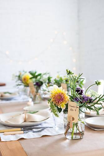 Gläser mit Blumen als Tischdeko