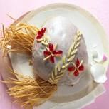 Osterbrot mit Stroh-Deko auf einem Teller drapiert