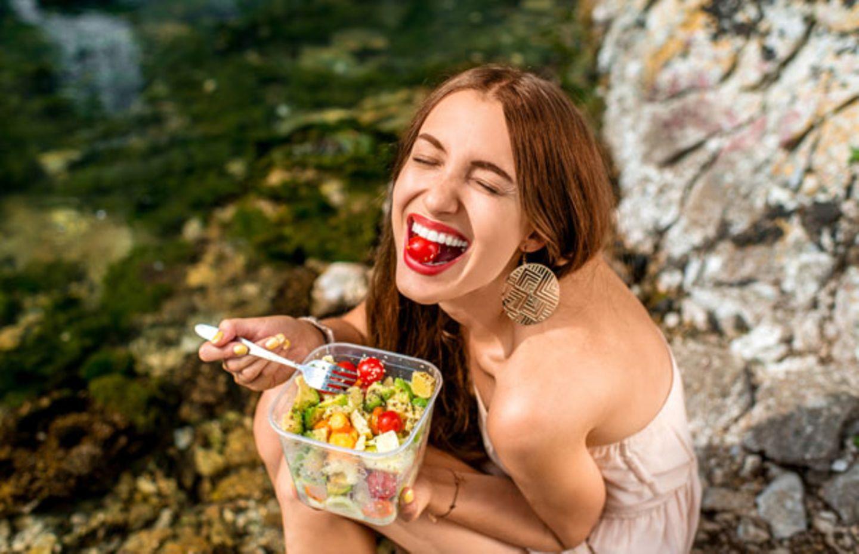 Pegan: Eine Frau mit Tomate im Mund grinst in die Kamera