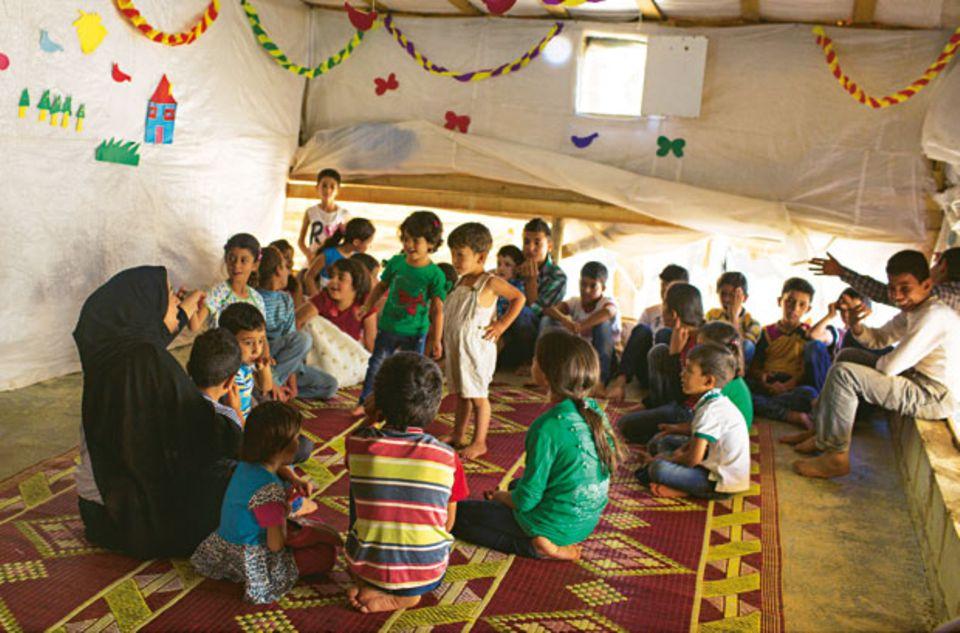 Rula (links) ist eine der Leiterinnen des Kinderraums im Camp. Hier sollen die Kinder nach der Flucht stabilisiert werden. Manche brauchen Wochen, bis sie sich allein hierher trauen. Ansonsten gibt es für sie keine kindgerechte Beschäftigung im Camp. Viele arbeiten mit sechs Jahren bereits auf dem Feld.
