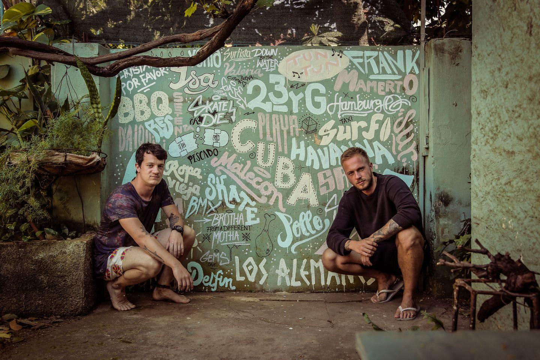 """Zum Bild: Johannes """"Jo"""" Riffelmacher und Thomas """"Cozy"""" Kosikowski (v.l.) vor einer Graffiti-Wand in Havanna, Kuba. """"Salt & Silver"""" - das sind die Freunde Johannes """"Jo"""" Riffelmacher und Thomas """"Cozy"""" Kosikowski. Zusammen bringen sie Anfang Juni 2015 das gleichnamige Kochbuch """"Salt & Silver Lateinamerika: Reisen - Surfen - Kochen"""" heraus. Voll mit den besten Rezepten Lateinamerikas, liefert das Buch außerdem Bilder und Berichte zu den besten Surf-Spots entlang der pazifischen und karibischen Küste Mittel- und Südamerikas. Als Krönung erzählen die beiden Macher abenteuerliche Anekdoten, die geschehen, wenn man die Nase zu tief in die Töpfe fremder Kulturen steckt. """"Salt & Silver"""": Gesagt, geplant, getan! Johannes und Thomas kamen zwar wegen der Arbeit nach Hamburg, doch auf Dauer reichte ihnen das nicht. Sie wollten ihre Leidenschaften Reisen, Surfen und Kochen zu ihrem Lebensmittelpunkt machen. So entstand vor etwa drei Jahren das """"Salt & Silver""""-Konzept. Die Wortkombination steht für das Meer, Surfen, aber auch für die Würze und die Messer, die zum Kochen benötigt werden. """"Wir haben schon immer gerne gekocht und unsere Skills stetig versucht zu erweitern. Als der Gedanke aufkam, gemeinsam durch Lateinamerika zu reisen, hat sich der Gedanke zum Konzept konkretisiert."""" Gesagt, geplant, getan! Im Januar 2014 starteten die beiden Jungs von Hamburg aus in Richtung Lateinamerika. Zwölf Monate dauerte ihre Reise. Bei der Rückkehr hatten sie die besten Rezepte und tolle Erfahrungen aus Kuba, Mexiko, Nicaragua, Costa Rica, Panama, Equador, die Galapagos-Inseln, Peru und Chile mit im Gepäck. """"Salt & Silver"""" - mehr als nur ein Buch! Schon während der Reise haben die surfenden Köche auf ihr Projekt aufmerksam gemacht. Täglich veröffentlichten sie Fotos, Videos und Rezepte über ihren Blog und die Social Media-Kanäle Facebook, Instagram und Vimeo. Seit sie zurück in Deutschland sind, ist es nicht ruhiger um sie geworden. Mittlerweile haben Jo und Cozy ihre eigene Firma gegründet, """