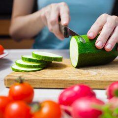 Gesunde Ernährung: Frau schneidet Zucchini
