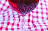Mediterrane Diät: Ein Glas Rotwein auf karierter Tischdecke