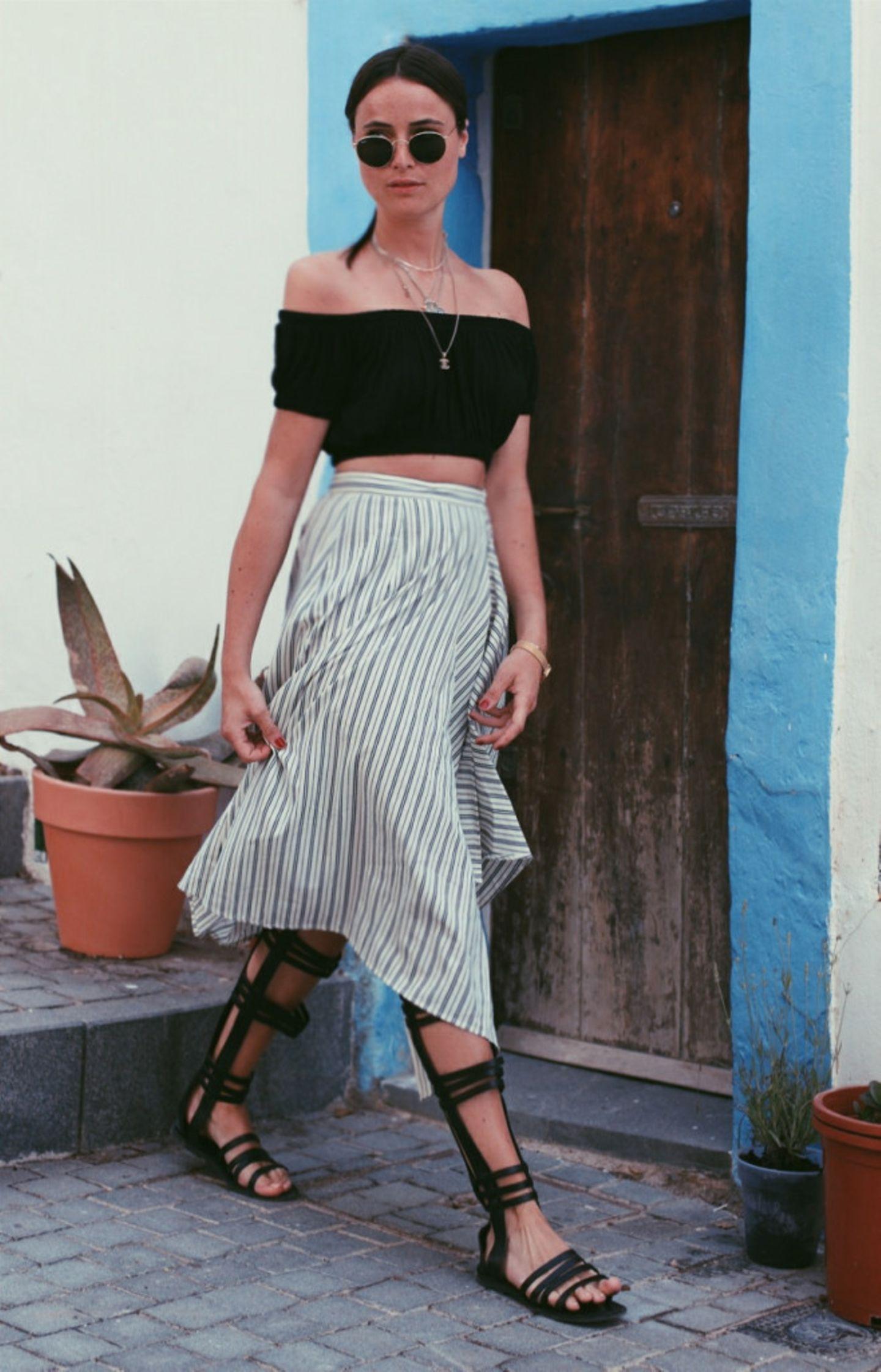 """Bei Lena von Blogger Bazaar dürfen diesen Sommer auf keinen Fall die Gladiator-Sandalen fehlen: """"Auch wenn sie ein wenig an Forrest Gumps Sprint mit Beinschienen erinnern, dienen sie als absoluter Eye-Catcher und machen das Outfit auf Anhieb spannender. Dazu darf es dann gerne ein wenig mädchenhafter zugehen. Kombiniert mit einem Rock und Off-Shoulder Top, wird der Look abgerundet und bringt sogar noch etwas sommerlichen Latinaflair einher."""""""