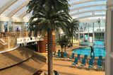 """Wo bei vielen Kreuzfahrtschiffen ein offenes Sonnendeck viel Platz einnimmt, ist auf der """"Aida Prima"""" ein Dach drüber: Der mit einer speziellen Luftfolie überdachte Beachclub verspricht konstant sommerliche Temperaturen von 25 bis 27 Grad - und garantiert Regenfreiheit."""