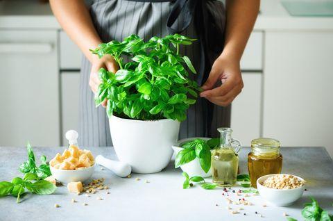 Basilikum länger frisch halten: Frau arbeitet mit Basilikum in der Küche