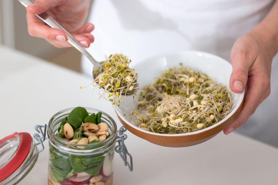 Sprossen auf den Salat geben