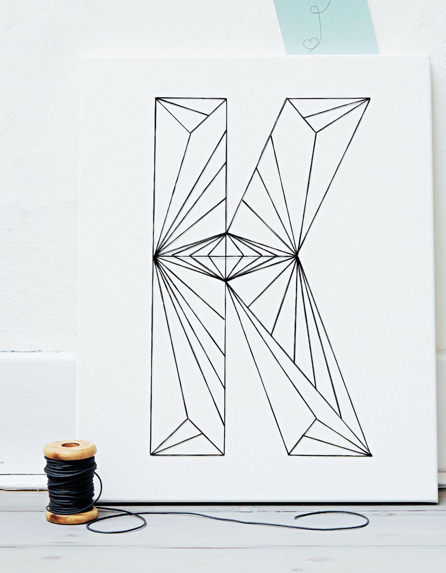 """Ob auf Tassen, Kissen oder Möbeln: Typografie ist Trend, und mit unseren kreativen Ideen kannst du Buchstaben zum Deko-Statement machen - genäht, gesteckt, lackiert, gestempelt ...      Fadenletter        Erst zeichnen, dann von Hand aufnähen - dieses kleine Kunstwerk verlangt ein klein bisschen Fingerspitzengefühl.      40 cm x 50 cm      Material:1 Keilrahmen, 40 x 50 cm (z. B. über www.staffeleien-shop.de), mehrfädiges Baumwoll-Stopfgarn in Schwarz (z. B. """"Anchor Stranded Cotton Mouliné"""" von Coats), Stopfnadel, Schere, Bleistift, Karopapier, Geodreieck, Kopierer, Stecknadeln, Maskingtape."""