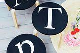 """Initial-Hocker        Sitzordnung mal anders: Hier bekommt jeder sein eigenes Schemelchen - mit auflackiertem Buchstaben.      Ø 35 cm, Höhe 45 cm      Material:Hocker (z. B. """"Frosta"""" von Ikea), Mattlack in Schwarz und Weiß, glatte und festere Dokumentenhüllen, Cutter, Kopierer, Computer, Pinsel, kleiner Farbroller, Papier, Maskingtape, Schere.        So wird's gemacht:Sitzfläche abschrauben und mit schwarzem Mattlack lackieren, trocknen lassen.  Gewünschten Buchstaben mit dem Computer (hier: Schriftart """"Big Caslon"""") ausdrucken und auf ca. 23 cm Höhe mit dem Kopierer vergrößern. Das Papier mit dem Buchstaben mit Maskingtape auf eine Hälfte einer Dokumentenhülle kleben und vorsichtig den Buchstaben aus der Folie herausschneiden. So erhält man eine Folienschablone fürs Bemalen des Hockers."""