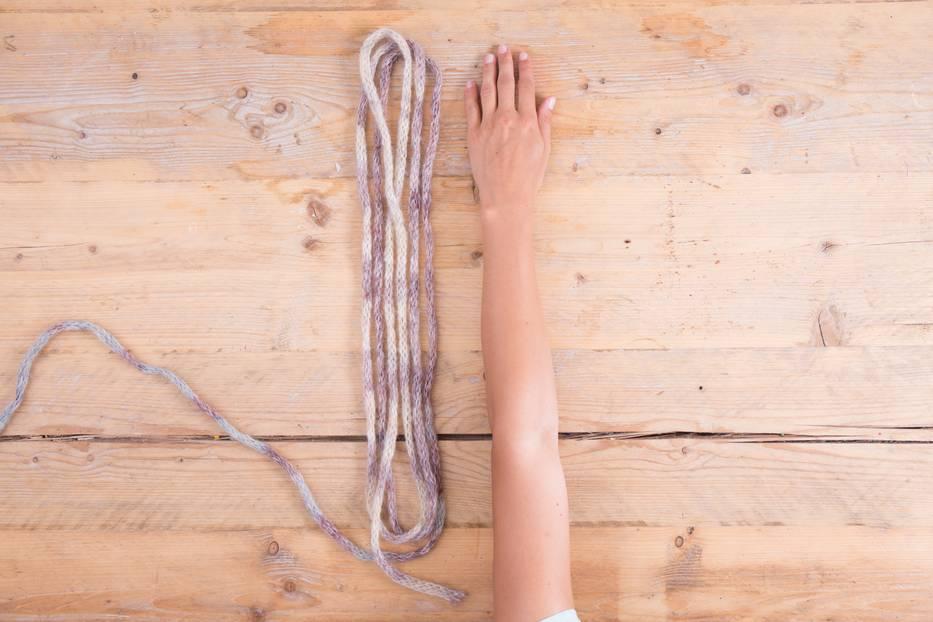 Um eine Wolldecke mit einer Breite von ca. einen m anzuschlagen, solltest du ca. 10 Armlängen Wolle bereithalten.