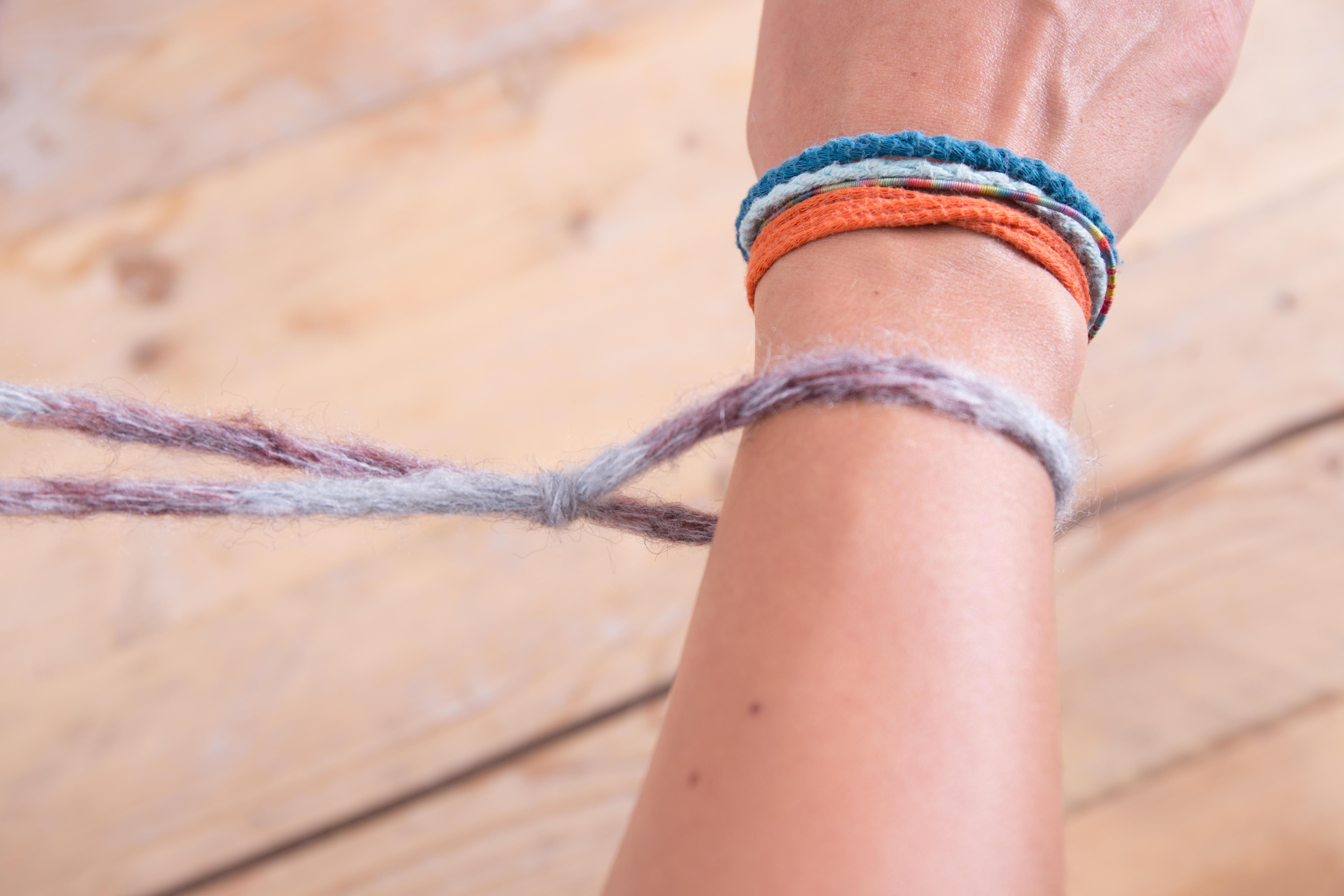 Die Schlaufe kannst du nun um deinen Arm legen. Da sie in der Größe verstellbar ist, ziehe sie nur ein bisschen zu. Sie darf ruhig locker an deinem Arm liegen.  hier kommt nämlich ein wichtiger Aspekt des Strickens: Selbst wenn die Masche zunächst nicht über deinen Handteller passen würde, kann sie direkt vor dem Abstricken leicht gelockert werden, da der Arbeitsfaden direkt mit ihr verbunden ist.