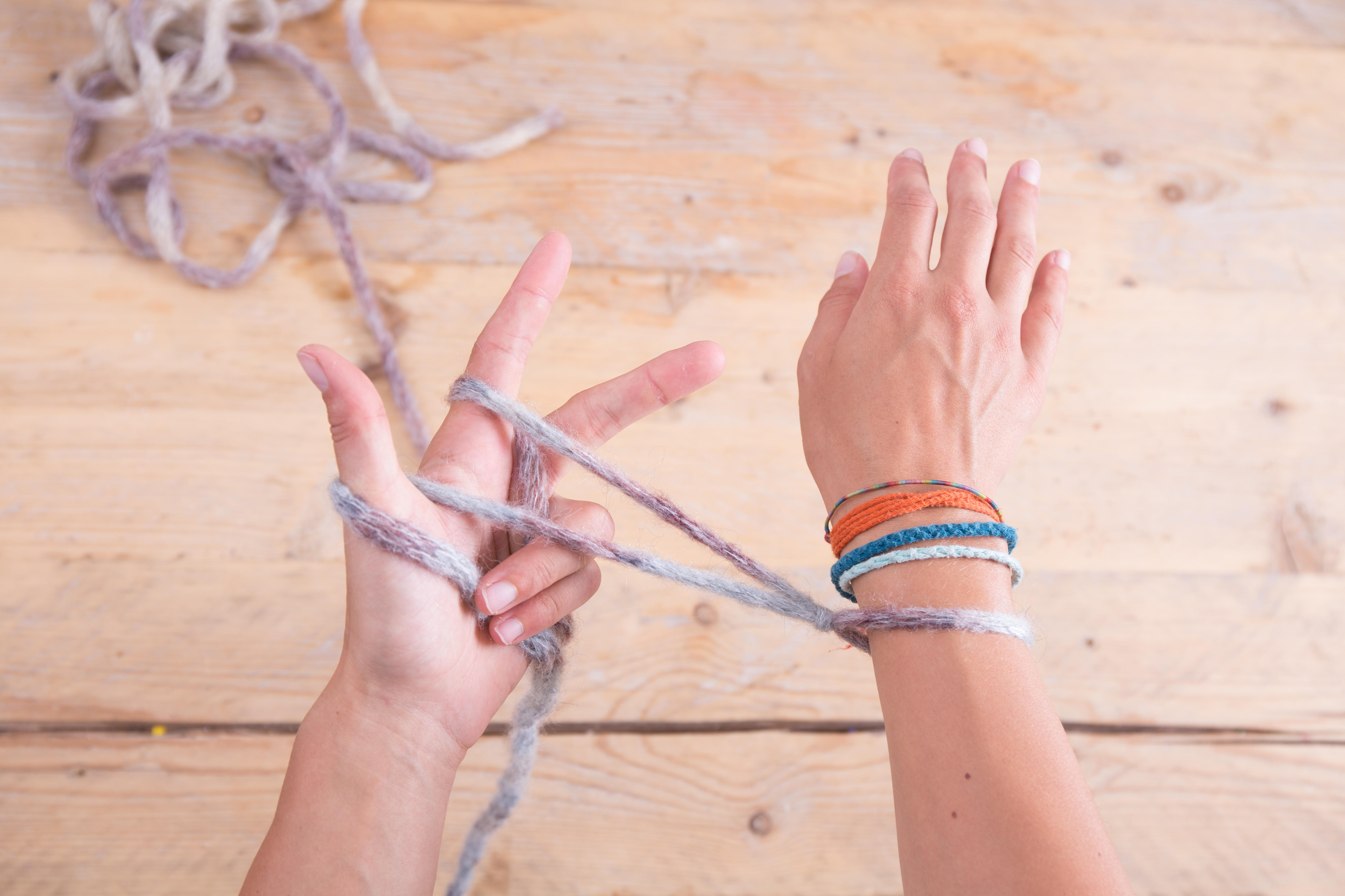 Mit dem Ringfinger und dem kleinen Finger hältst du die beiden losen Fadenenden fest.