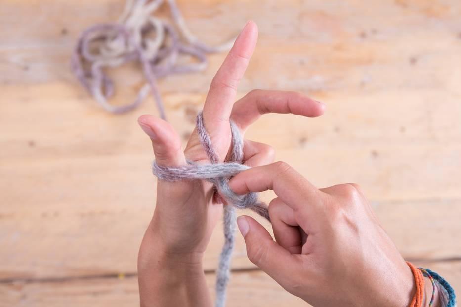 Du holst diesen Faden nun unter der Daumenschlaufe hervor. Dadurch bildet sich eine weitere Schlaufe, die du dir einfach über den rechten Arm streifst.