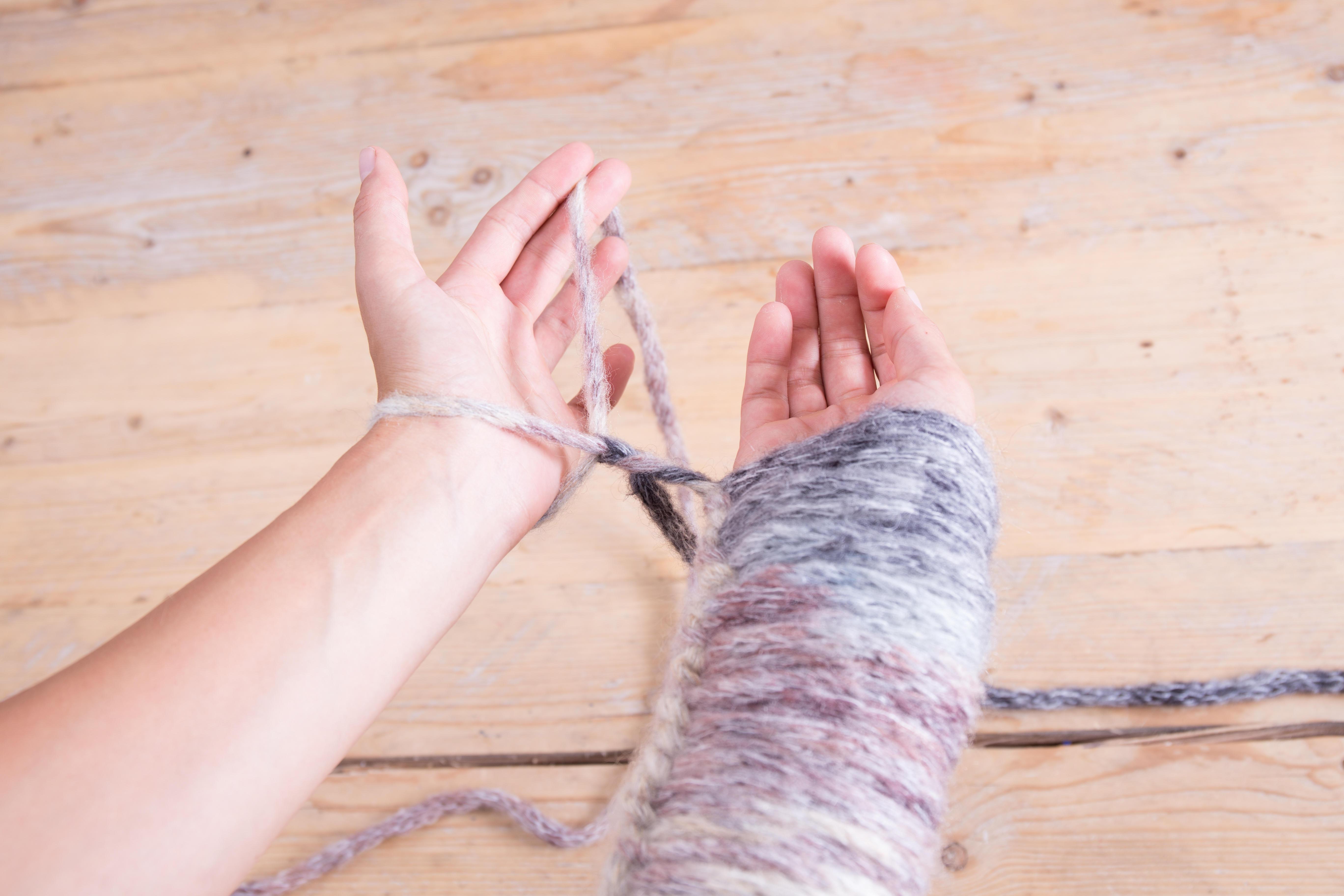 Nun ruckelst du ein bisschen mit den Fäden, bis die Masche leicht am Arm anliegt.