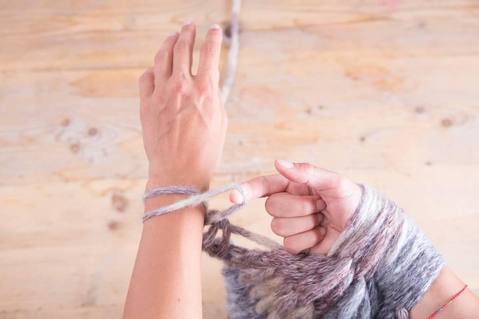 Nun nimmst du die erste Masche (also die, die weiter hinten auf deinem Arm liegt), ziehst sie über die vordere Masche und lässt sie von der Hand gleiten.